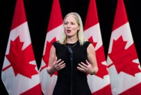 Honourable Catherine McKenna speaking in front of 4 Canadian flags