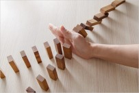 Hand blocking dominos from falling