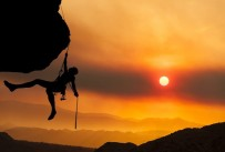 a person rock climbing at sunrise