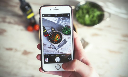 mobile phone in hand displaying a food picture in an influencer program
