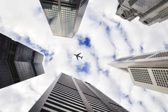 View of sky with skyscrapers and flying plane