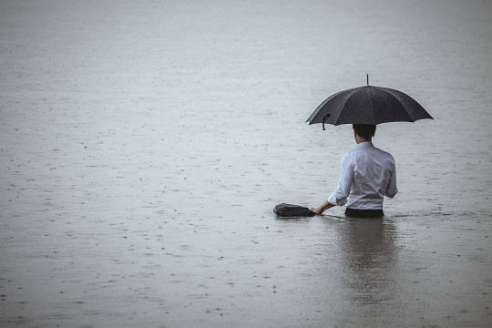Man standing in water with an umbrella