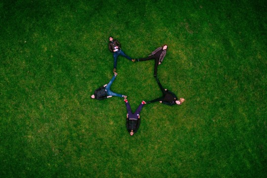 Drone shot of people laying on grass