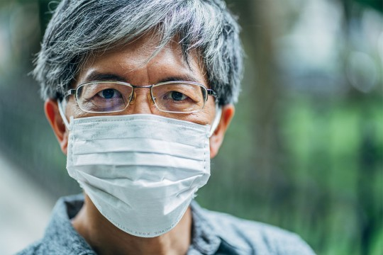 Asian man wearing a flu mask