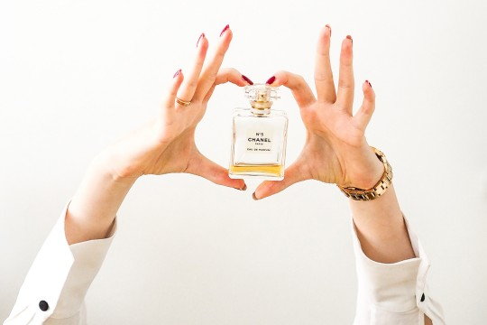 Hands holding a bottle of Chanel perfume