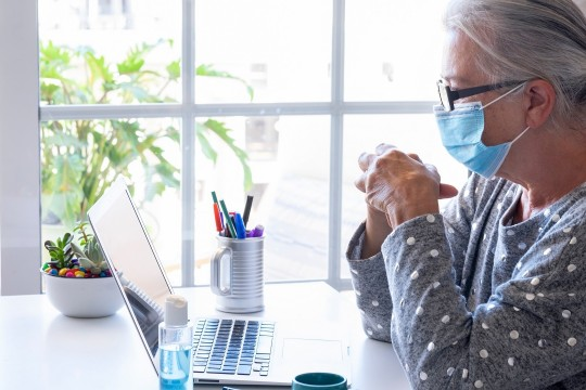 Elderly woman wearing a mask sitting in front of a computer