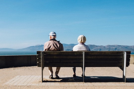 elderly couple on bench looking at the ocean