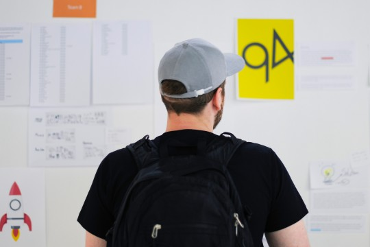 Designer standing in front of work on a wall