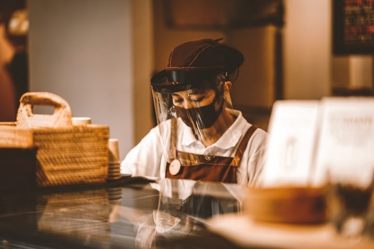 Foodservice worker with mask and visor