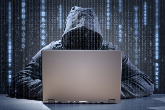 hacker behind computer with matrix code