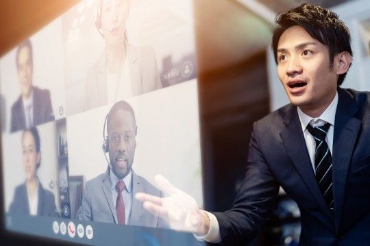 Man in suit in front of screen with virtual meeting