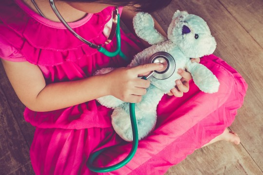 Young girl putting a stethoscope on a teddy bear