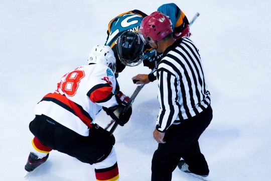 Hockey players faceoff with referee