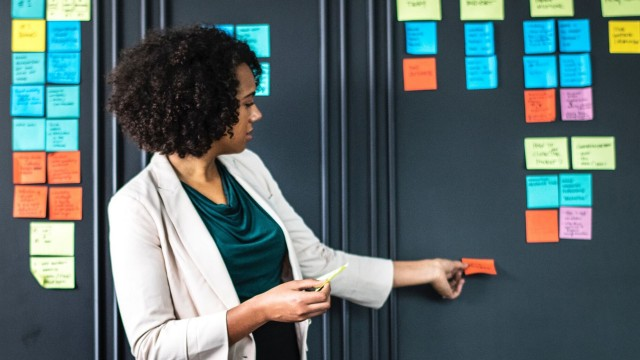 women sticking a post-it on a wall