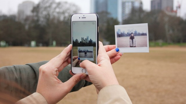 hand holding a picture while someone takes a photo with a smartphone